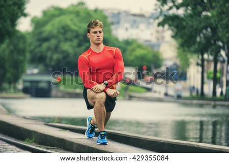 Young athletic man stretching outside - stock photo