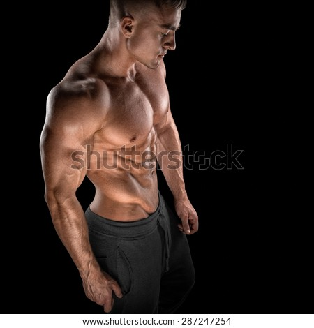 Young athletic man torso showing six pack abs. Strong bodybuilder with six pack, perfect abs, shoulders, biceps, triceps and chest - stock photo
