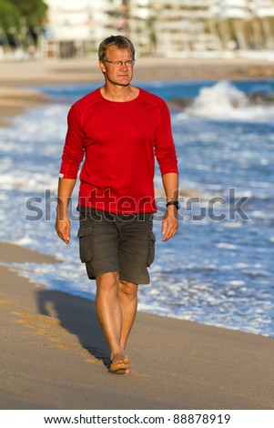 Young athletic man walks on the beach - stock photo