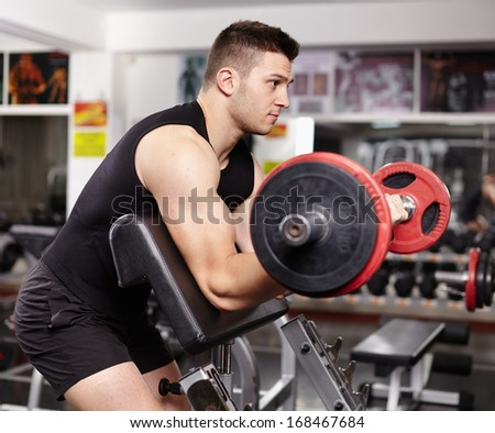 Young athletic man working his biceps at preacher curl bench at the gym
