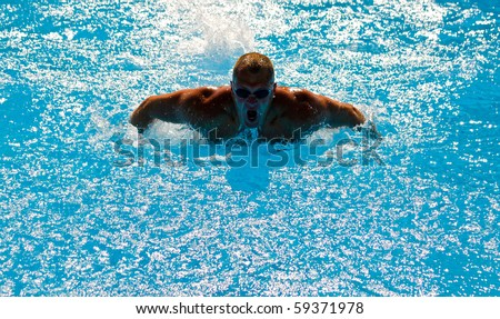 Young athletic man working out swimming in pool