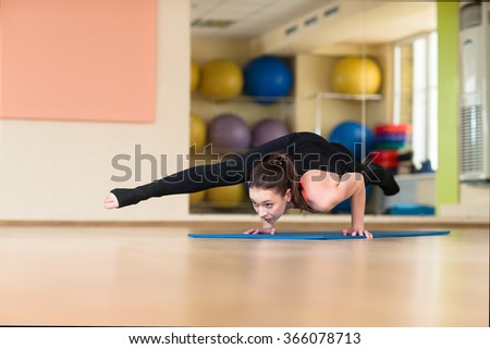 Young athletic woman doing yoga pose in Bakasana Crane Pose, Crow Pose. Indoor gym.