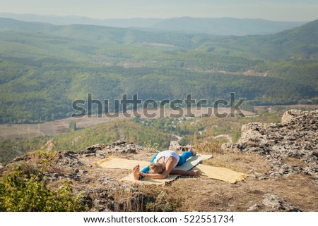 Young athletic woman doing yoga stretching exercises on top of a mountain with a beautiful view