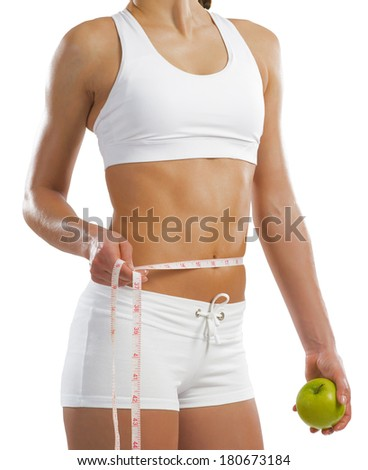 young athletic woman holding a green apple and measuring waist, isolated on white background - stock photo