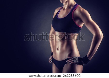 Young athletic woman on a black background - stock photo