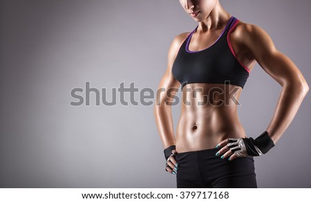 Young athletic woman on a gray background