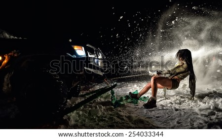 young athletic woman pulling car in winter - stock photo