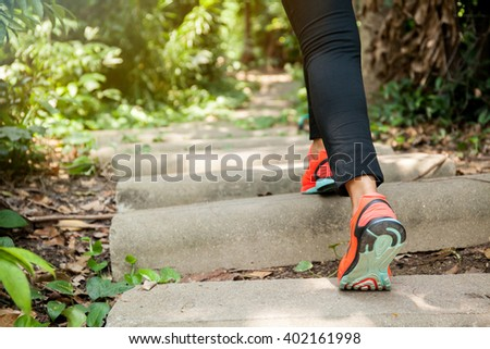 Young athletic woman running on forest trail