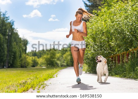 young athletic woman running on the road with white labrador, exercise outdoors - stock photo