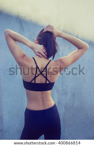 Young athletic woman stretching before exercise, muscular back to camera wearing sports bra and yoga pants - stock photo