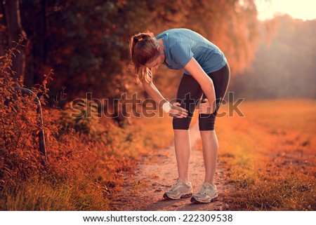Young athletic woman taking a break from training standing resting her hands on her knees on a rural track through lush farmland in a health and fitness concept - stock photo
