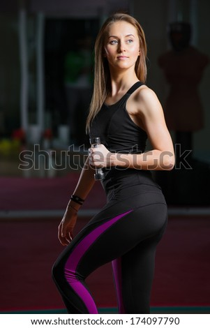 Young athletic woman with dumbbells - stock photo