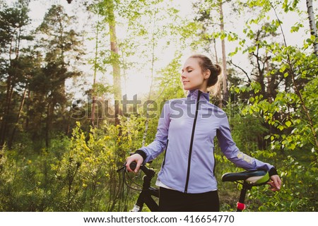 Young athletic woman with peaceful face with bicycle in forest  - stock photo
