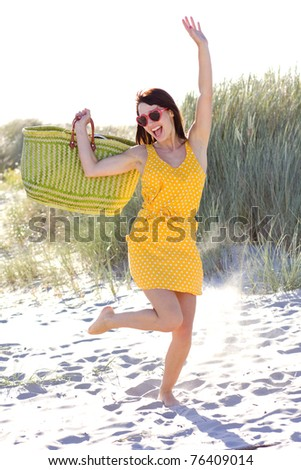 young atractive woman is holding green  bag on beach - stock photo