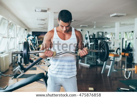 Young attractive adult man exercising and doing weight lifting at fitness gym. Sport training indoors.