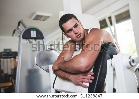 Young attractive adult man in a fitness gym. He rests between exercises and looking at side. Sport training indoors.