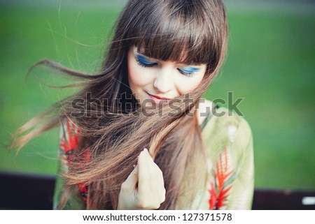 Young attractive adult woman outdoors holding her hear - stock photo