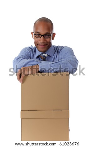 Young attractive African American businessman in office sitting behind the storage boxes with the hands against them . Studio shot. White background. - stock photo