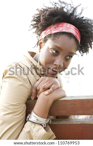 Young attractive african american woman being thoughtful while sitting on a bench in a city park.