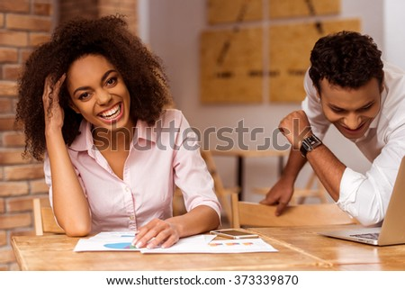 Young attractive Afro-American business couple using laptop and laughing while working in cafe - stock photo