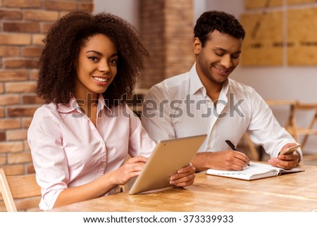 Young attractive Afro-American business couple using tablet, making notes, looking in camera and smiling while working in cafe