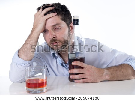 young attractive alcoholic business man with beard  wearing blue shirt and tie drunk and drinking  Scotch or Whisky looking wasted on office desk at work isolated on white background - stock photo