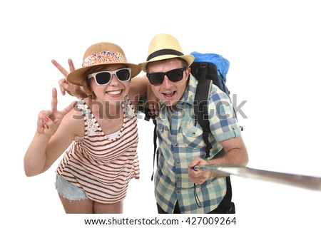 young attractive American couple taking selfie photo portrait together with mobile phone and stick isolated on white background wearing tourist backpack chic hat and sunglasses in trendy look - stock photo