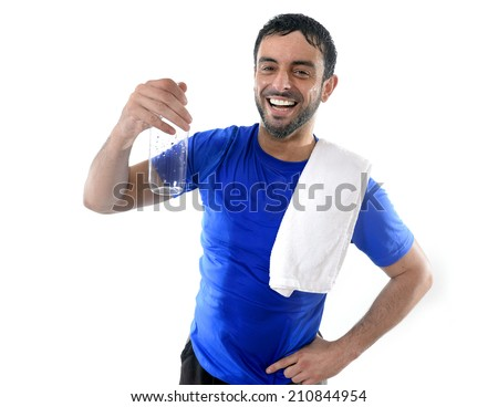 young attractive and athletic sport man with gym towel smiling happy all wet and drinking water bottle after training  isolated on white background - stock photo
