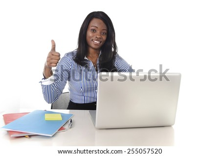 young attractive and black African American ethnicity woman working at computer laptop at office desk smiling happy giving thumb up in business success career concept - stock photo