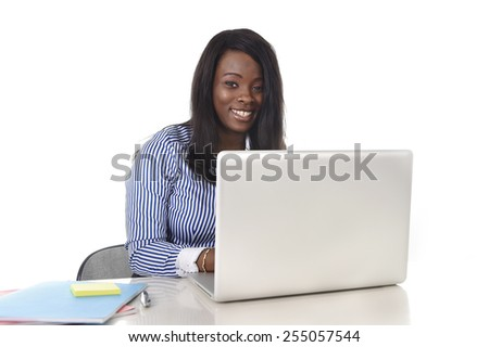 young attractive and black African American ethnicity woman working at computer laptop at office desk smiling happy in business success career concept - stock photo