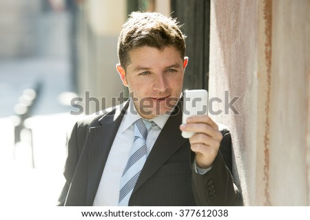 young attractive and busy businessman with blue eyes wearing suit and tie using mobile phone sending message or consulting internet leaning on street wall outdoors in the morning - stock photo