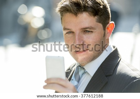 young attractive and busy businessman with blue eyes wearing suit and tie using mobile phone sending message or consulting internet on street outdoors in the morning - stock photo