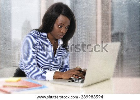 young attractive and efficient black ethnicity woman sitting at business district office computer laptop desk typing concentrated isolated on white background in career success concept  - stock photo