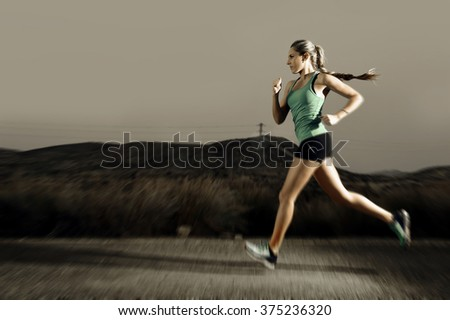 young attractive and fit sport woman running outdoors on asphalt road in mountain landscape on evening with harsh light in fitness workout training shot in motion blurred advertising style