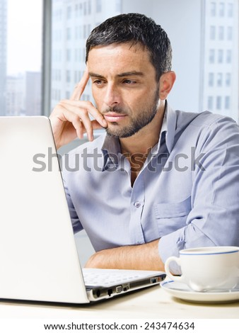 Young attractive and handsome businessman working on computer laptop with coffee cup sitting at office desk in front of skyscraper window view looking thoughtful - stock photo