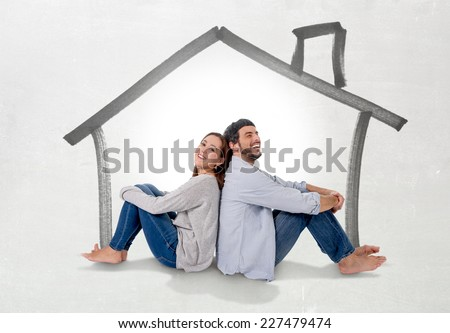 Young attractive and modern couple in love smiling happy together sitting on floor thinking and imaging their new house, home, flat or apartment in real state concept - stock photo