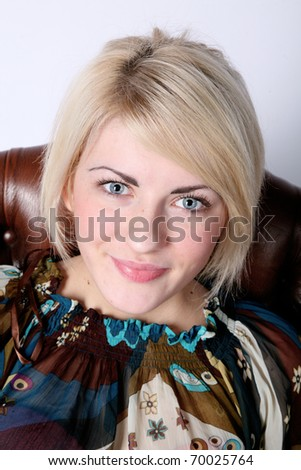 Young attractive and sexy blond female sitting on a chair