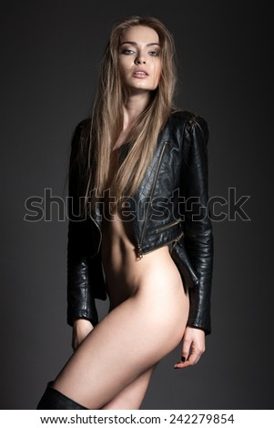 Young attractive and sexy female model with long hair and perfect makeup, in black leather jacket and boots, posing in studio topless and without other clothes