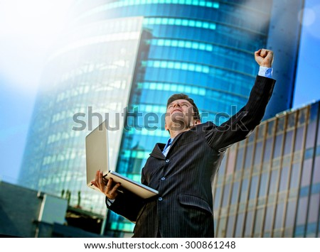 young attractive and successful businessman in suit and tie with computer laptop happy and excited doing victory sign celebrating success outdoor on financial district street