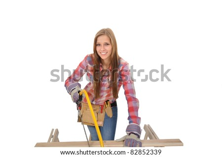 Young attractive artisan with hacksaw sawing a board - stock photo