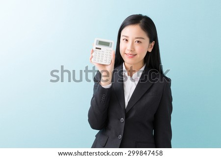 young attractive asian businesswoman having an electronic calculator - stock photo