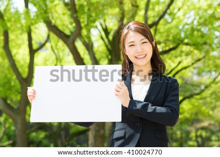 young attractive asian businesswoman holding blank white board - stock photo