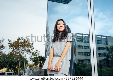 young attractive Asian businesswoman posing with her laptop on a background of a mirror wall of a skyscraper - stock photo