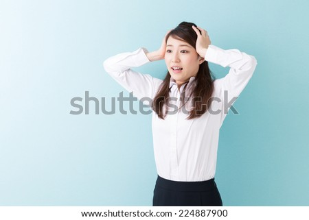 young attractive asian businesswoman who is surprised - stock photo