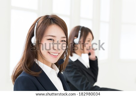 young attractive asian businesswoman with headset - stock photo