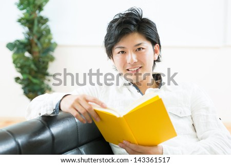 young attractive asian man who reads a book