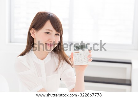 young attractive asian woman having an electronic calculator