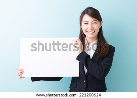 young attractive asian woman holding blank white board - stock photo