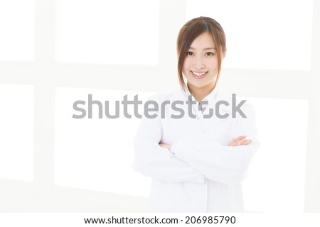 Young attractive asian woman in a white coat - stock photo