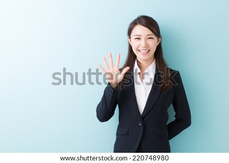 young attractive asian woman indicating the number five - stock photo